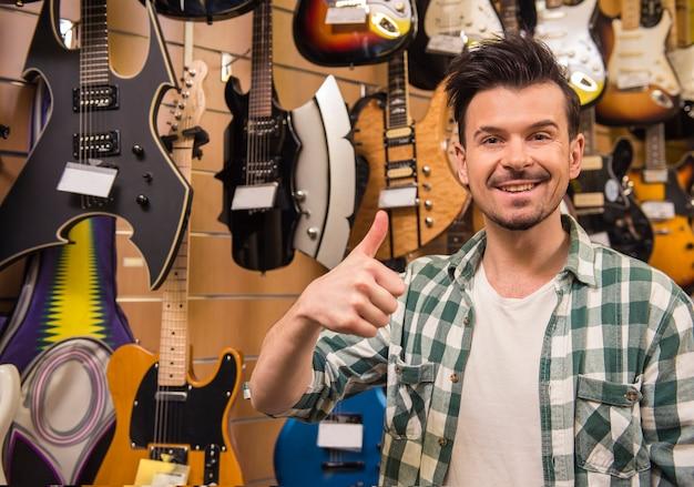 男はエレキギター店で親指を表示しています