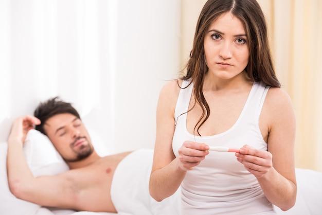 Расстроенная женщина смотрит в тест на беременность.