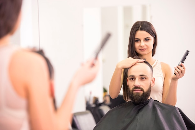 幸せな女性の美容師は、サロンでクライアントの髪を切っています。