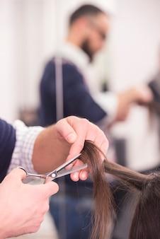 美容師は、美容院で女性の髪をカットします。