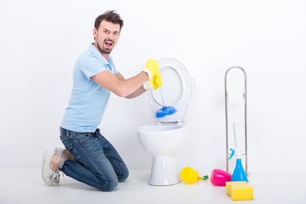 若い男がプランジャーでトイレの詰まりを取り除きます。