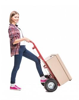 Молодая женщина с бумажной коробкой и ручной тележкой.