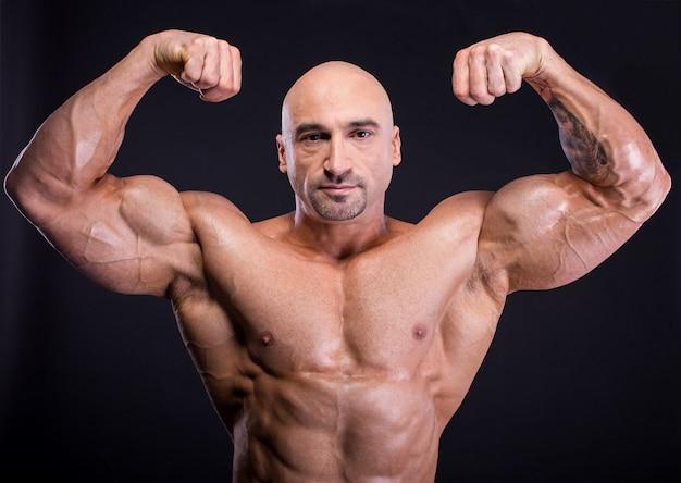 男は彼の完璧な筋肉の体を示しています。