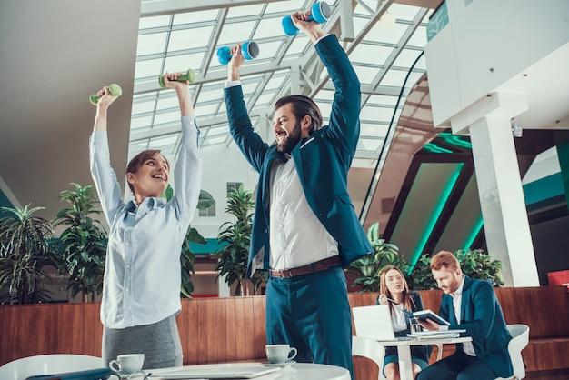オフィスでダンベルで運動をする労働者。