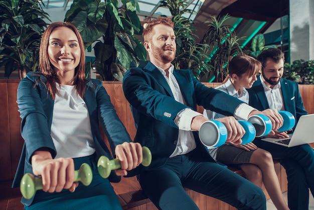 オフィスのベンチで運動する男性と女性の労働者。