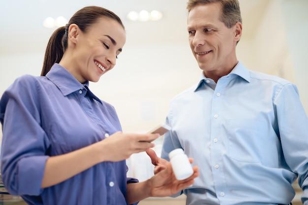 男と女は薬局で薬を選択します。