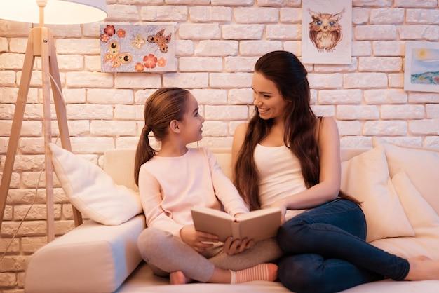 母と娘はラップトップで本を読んでいます。