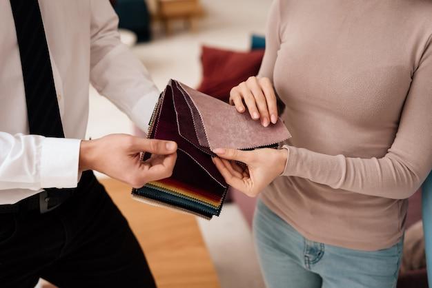 Менеджер показывает женщине образцы тканей для диванов.