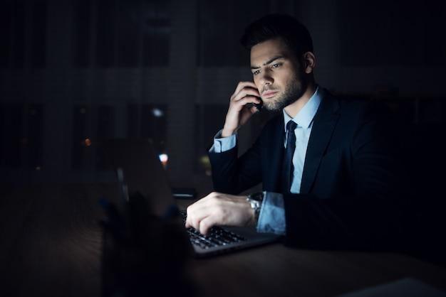 男は暗いオフィスでラップトップに座っています。