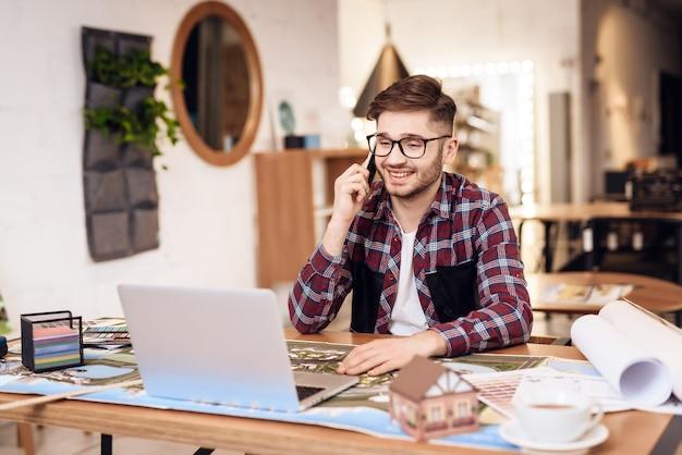 Фрилансер человек разговаривает по телефону на ноутбуке, сидя за столом.