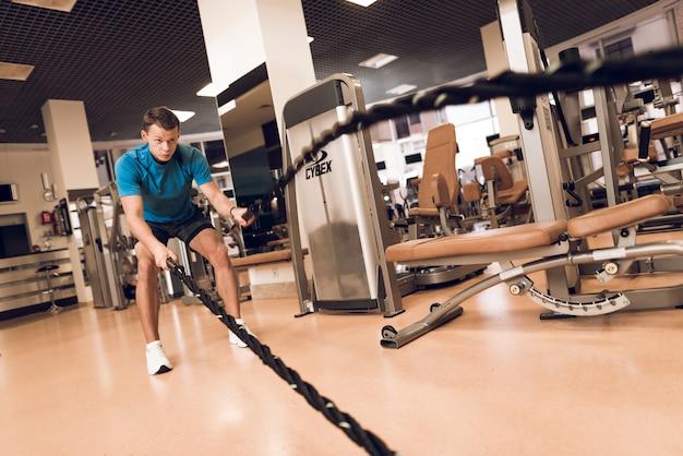 ジムでロープで運動をしている男。