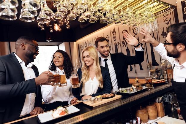 Четверо парней и девушек заказали пиво в баре.