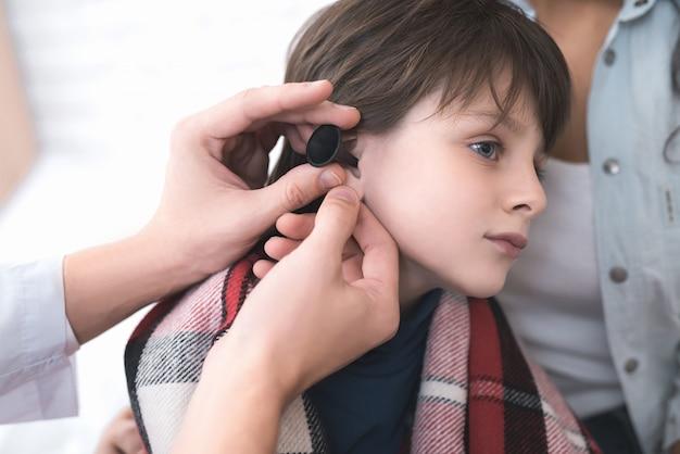 医者は病気の男の子の耳を調べます。