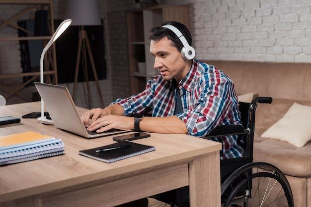 若い障害者が家で働いています。