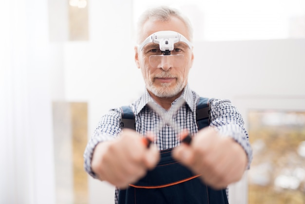Пожилой мужчина позирует на камеру с помощью отвертки.