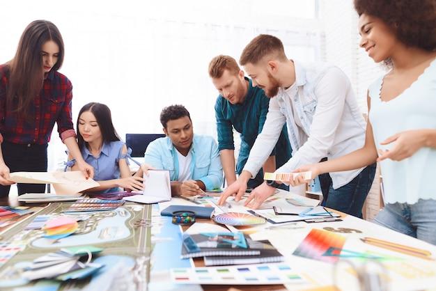 さまざまな国籍の若いデザイナーがブレーンストーミングに費やしている