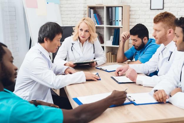さまざまな人種の医師のグループがテーブルで会っています。