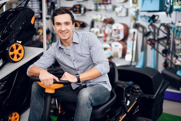 男が芝刈り機の車輪の後ろに座って笑顔。