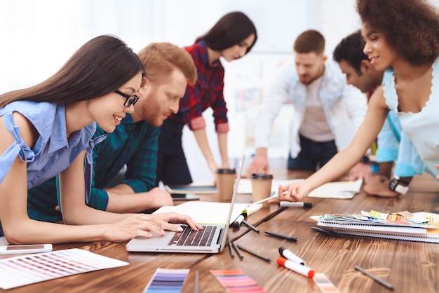 Группа молодых людей работают в команде в большом ярком офисе.