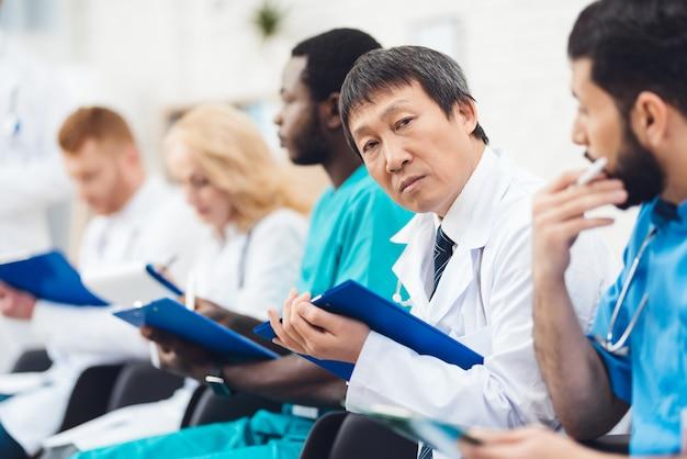 アジアの医師がカメラを見ます。