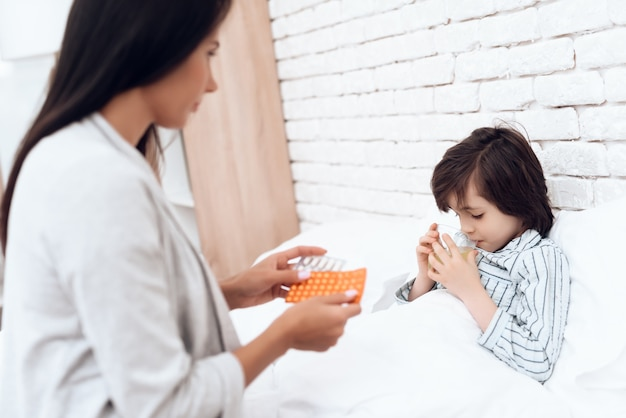お母さんは自宅で病気の息子に薬を与えます。