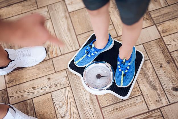 父親は体重計で息子の体重を量ります。
