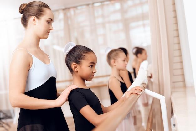 コーチは、小さな女の子がクラスで訓練するのを助けます。
