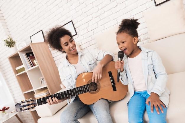 ママと小さな女の子が一緒に歌って、ギターを弾きます。