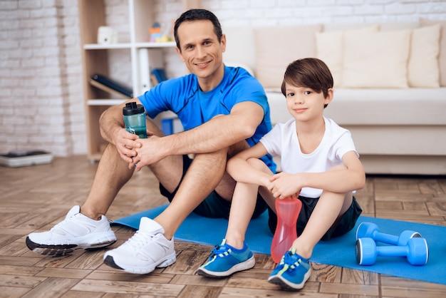 Отец и сын отдыхают после тренировки.