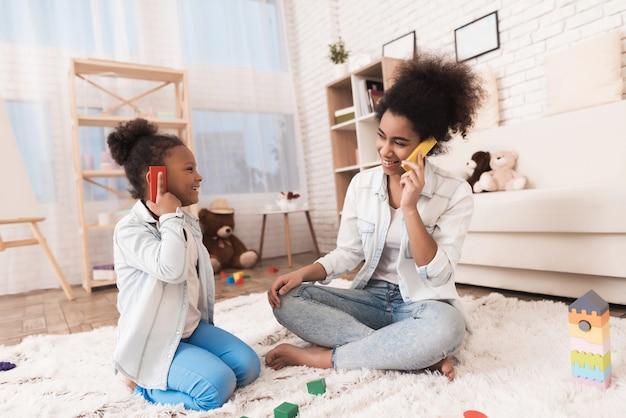 ママと娘は、木製キューブで床で遊んでいます。