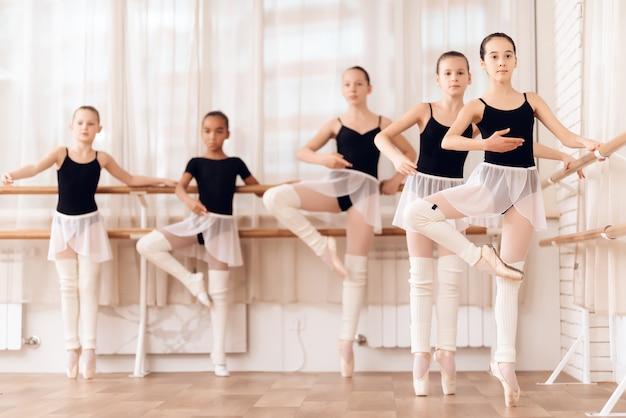 バレエクラスの若いバレリーナは、一緒にトレーニングします。