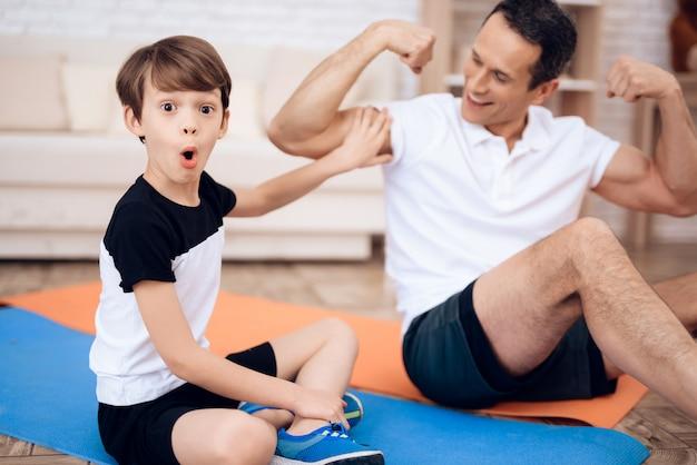 父は息子に筋肉を見せます。