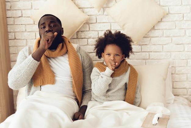 父と娘が自宅のベッドに座って咳。