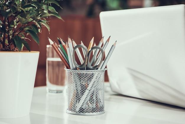 Закройте вверх по ящику с карандашами и компьтер-книжкой на столе в офисе.