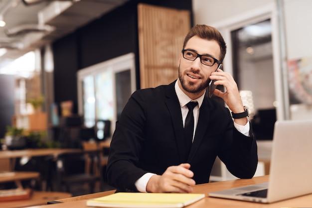 ビジネススーツを着た男が彼のオフィスで働いています。