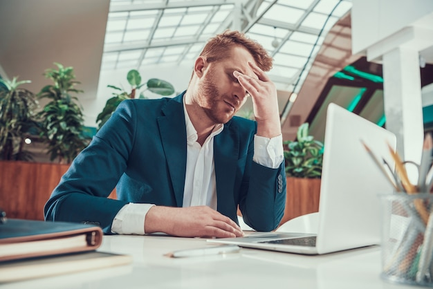 スーツの労働者の男は、オフィスの机で疲れています。