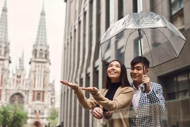 旧市街の男の子と女の子の雨の日のロマンチックな旅行。