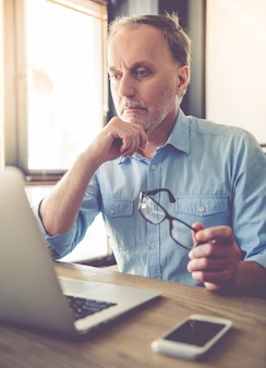 ハンサムな成熟した疲れたビジネスマンはラップトップを使用しています