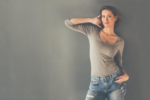 Женщина в сером боди и джинсах показывает телефон