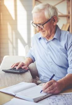 眼鏡の老人は電卓を使用しています。