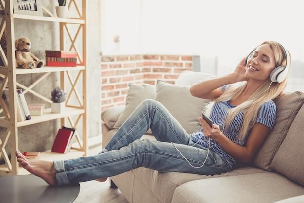 Девушка в наушниках слушает музыку с помощью смартфона