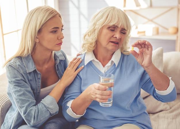 女の子は薬を飲んでいる悲しい古い母親を落ち着かせています