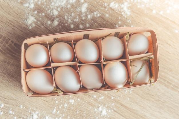 Свежие яйца в коробке для выпечки лежа на столе