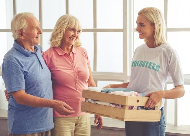 女性ボランティアは新しい服の箱を与えています