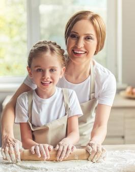 Милая девушка и ее мама в фартуках
