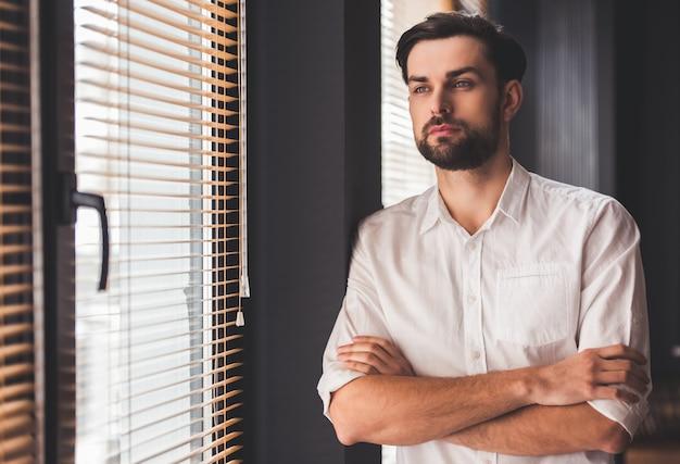 ハンサムな青年実業家は窓の外を見ています。