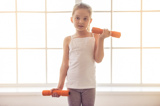 女の子はフィットネスホールでダンベルでワークアウトします。