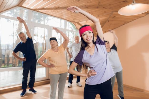 Группа пожилых женщин и мужчин, занимающихся лечебной гимнастикой.