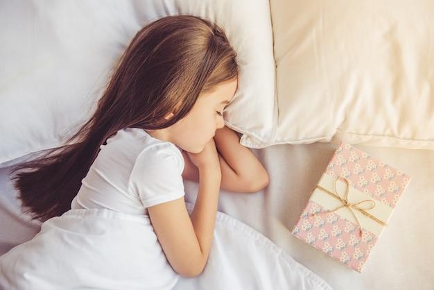 Очаровательная маленькая девочка спит в своей постели у себя дома