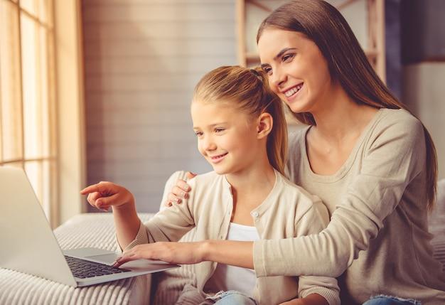 美しい母親と彼女の小さな娘はラップトップを使用しています